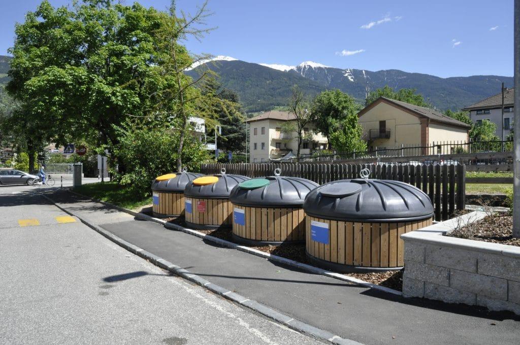 Quatre conteneurs semi enterré en bardage bois clair dans un village de montagne